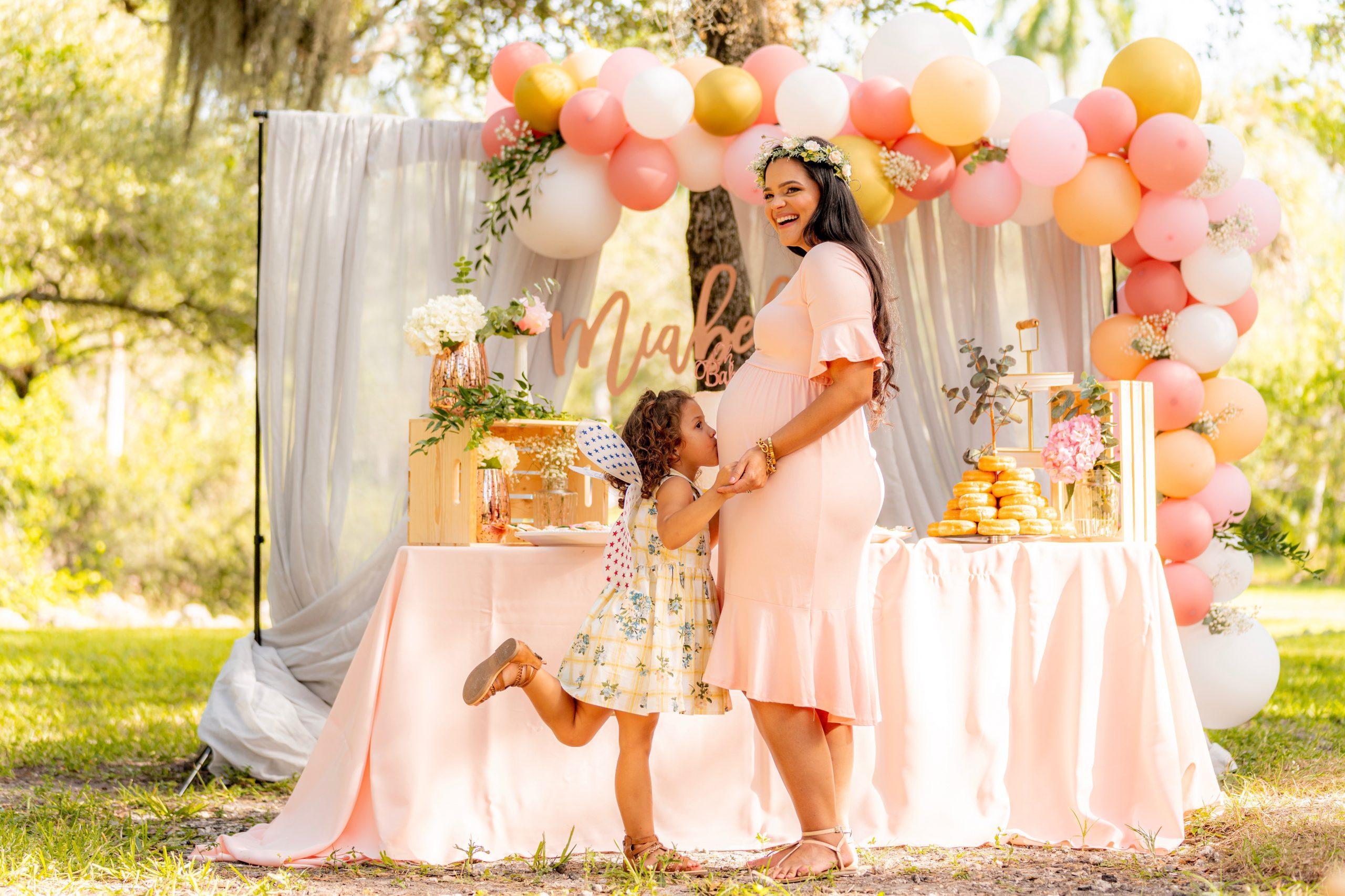 Une petite fille embrasse le ventre de sa maman à une baby shower