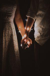 Des mains de mariés entrelacées avec une guirlande
