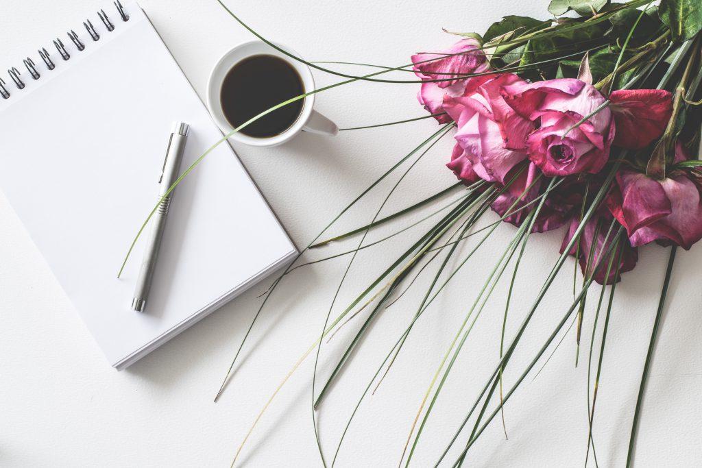 Un bouquet de fleurs à coté d'un carnet de note et d'un café