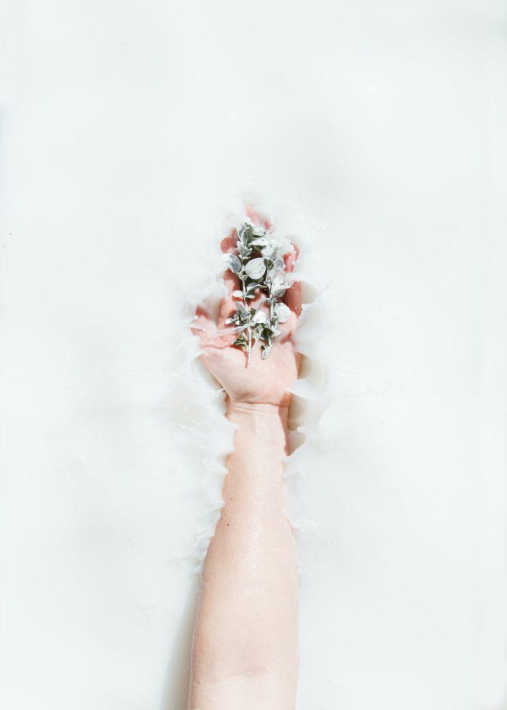 Une main tenant des fleurs dans de l'eau blanche