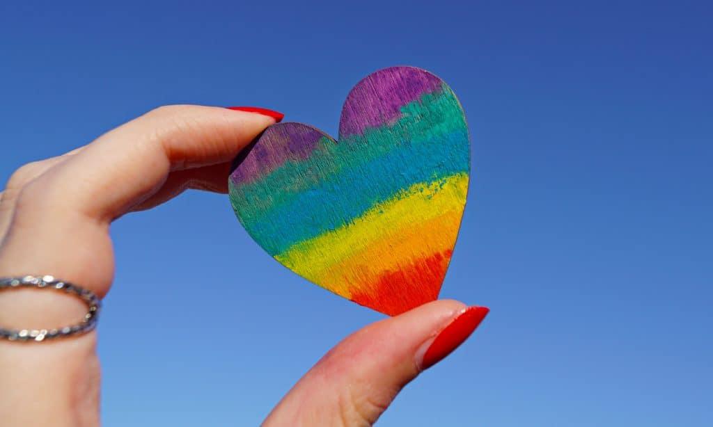 Coeur multicolore tenu entre des doigts