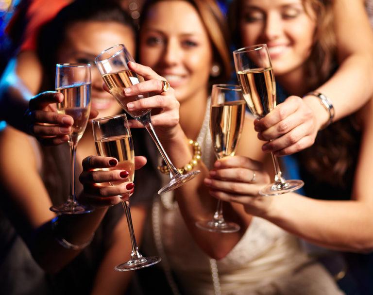 Groupe de filles faisant la fête trinquent avec des flûtes de vin mousseux